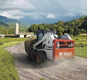 Bobcat S630 skid-steer loader with two-speed travel option on farm.