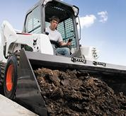 Bobcat skid-steer loader works along curb.