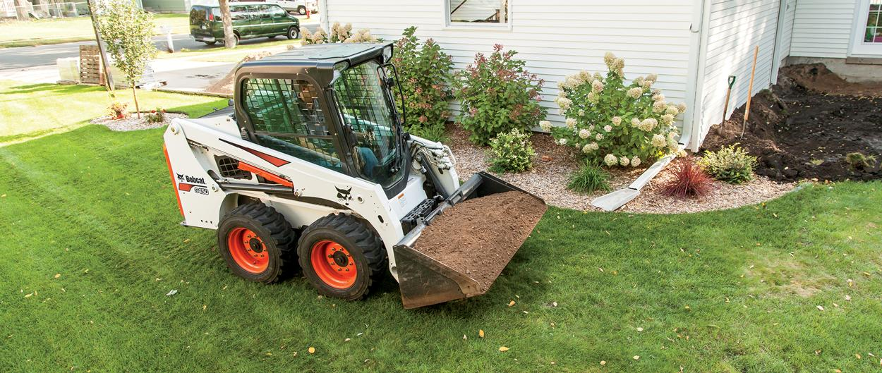 Bobcat S450 skid-steer loader moves dirt with a bucket attachment.