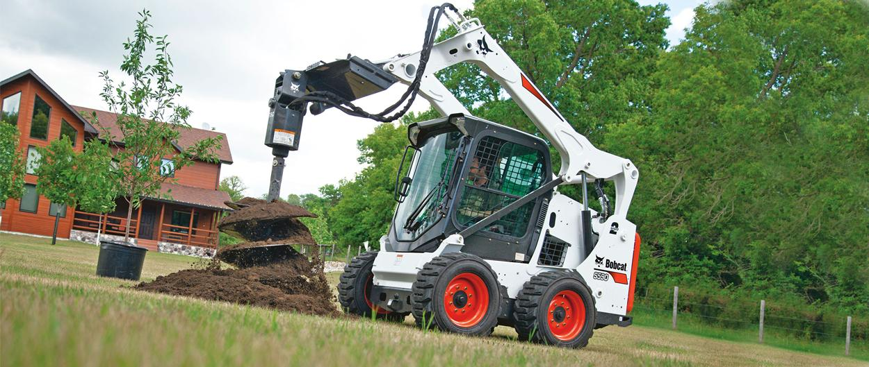 Bobcat S590 skid-steer loader and auger attachment digging a hole for tree planting