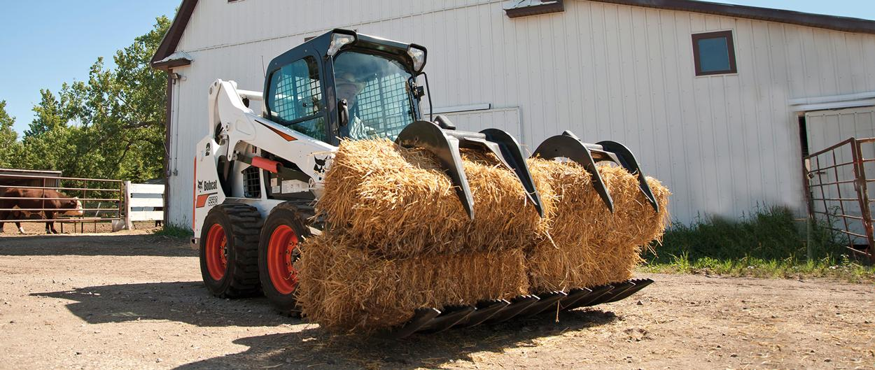 Bobcat S590 skid-steer loader with a bale fork attachment carrying a bail of hay on a farm road.