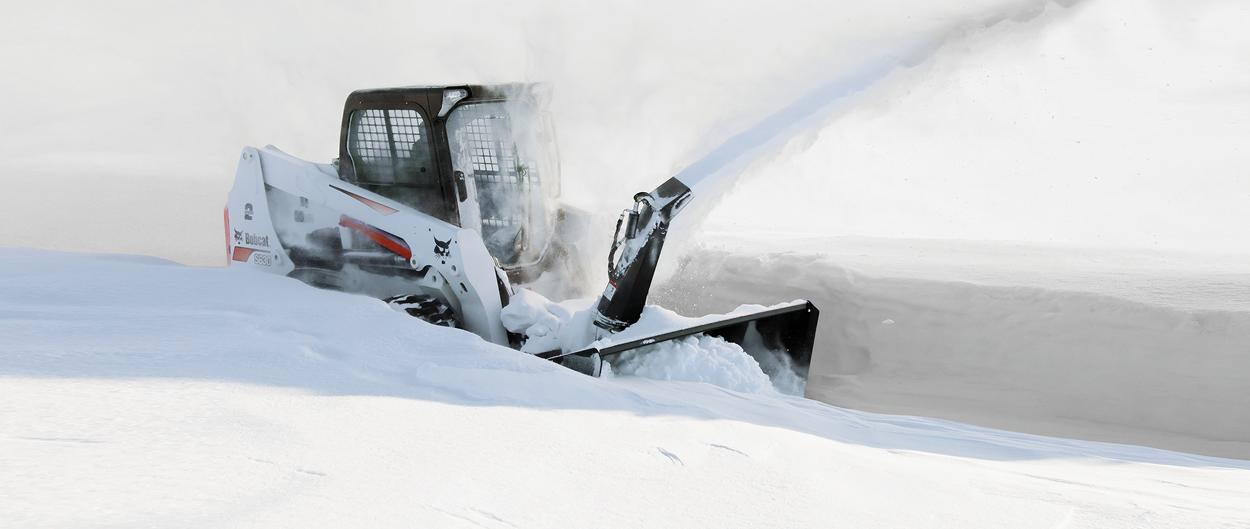 A Bobcat S630 and snowblower attachment blows snow.