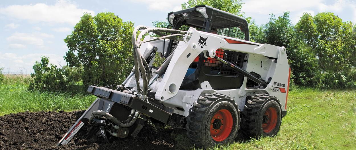 Bobcat S630 skid-steer loader with trencher attachment.