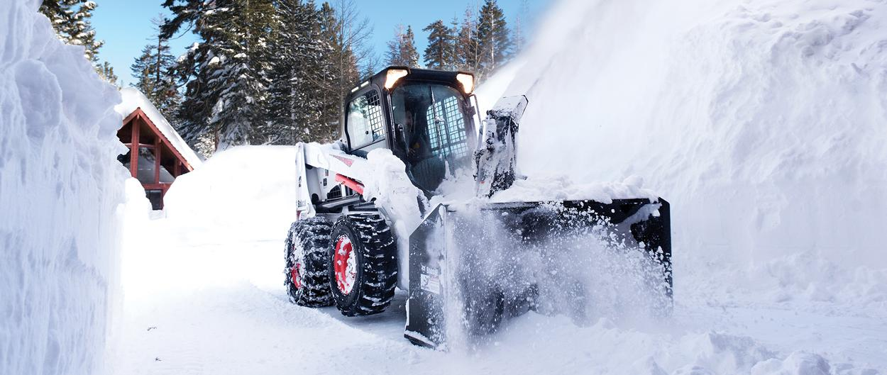 Bobcat S630 skid-steer loader and snowblower attachment removing snow near a cabin.