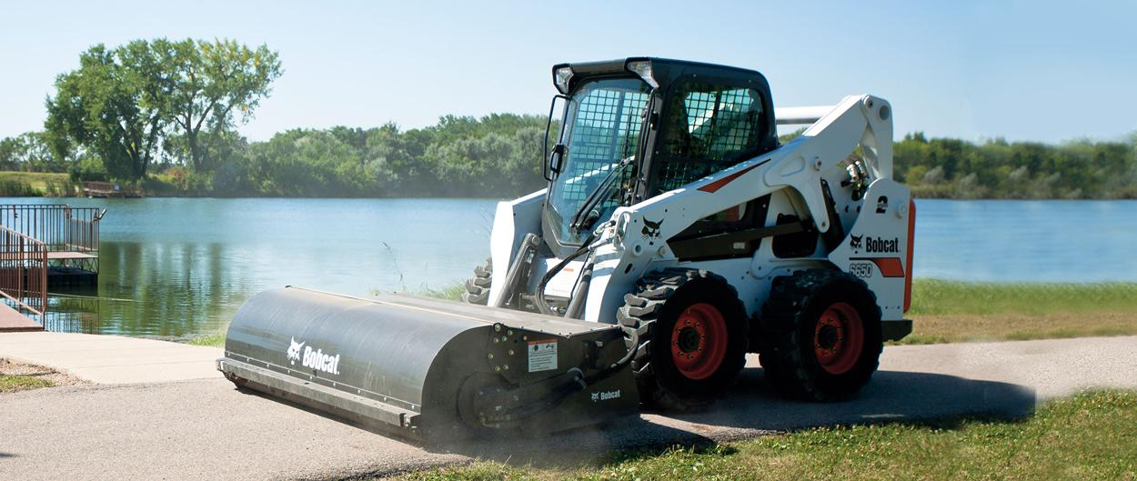 Bobcat S650 skid-steer loader and sweeper attachment cleaning dust and debris off a footpath