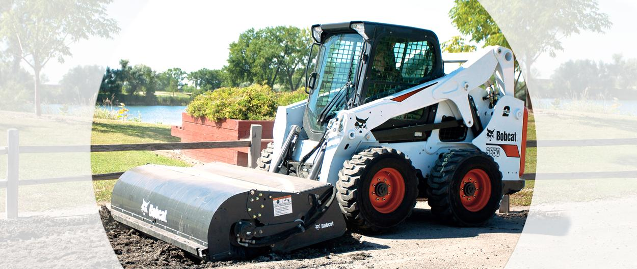 Bobcat S650 skid-steer loader with a sweeper attachment clearing debris on a footpath.