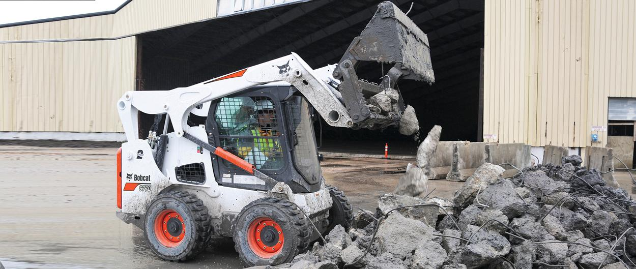 Bobcat S770 skid-steer loader and combination bucket attachment moving concrete debris.