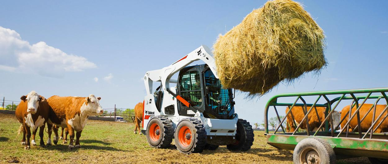 Bobcat S7700 skid-steer loader moving hay on a farm.