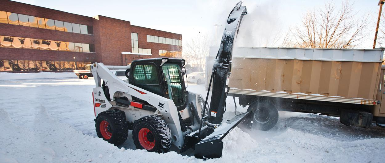Bobcat S850 skid-steer loader blowing snow into a truck.