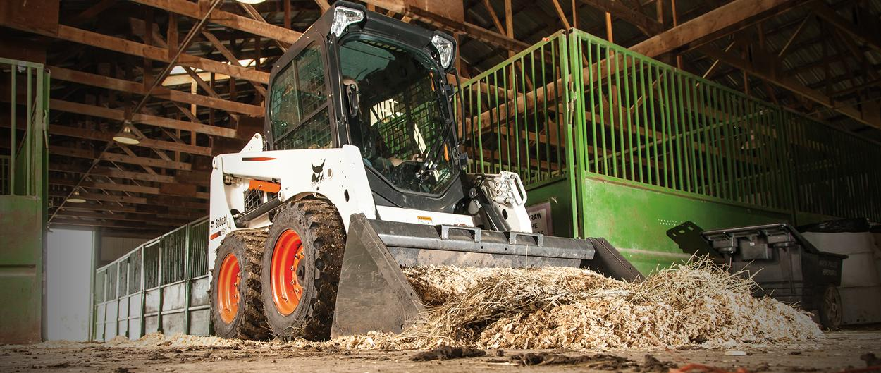 A Bobcat skid-steer loader pushes straw and manure inside a barn.
