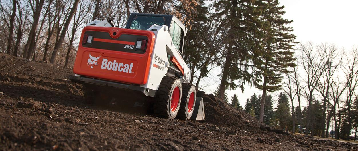 Bobcat S510 skid-steer loader scoops dirt.
