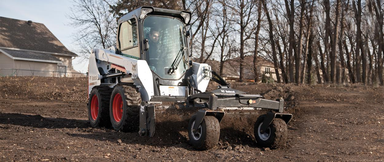 Bobcat S510 skid-steer loader with soil conditioner attachment.