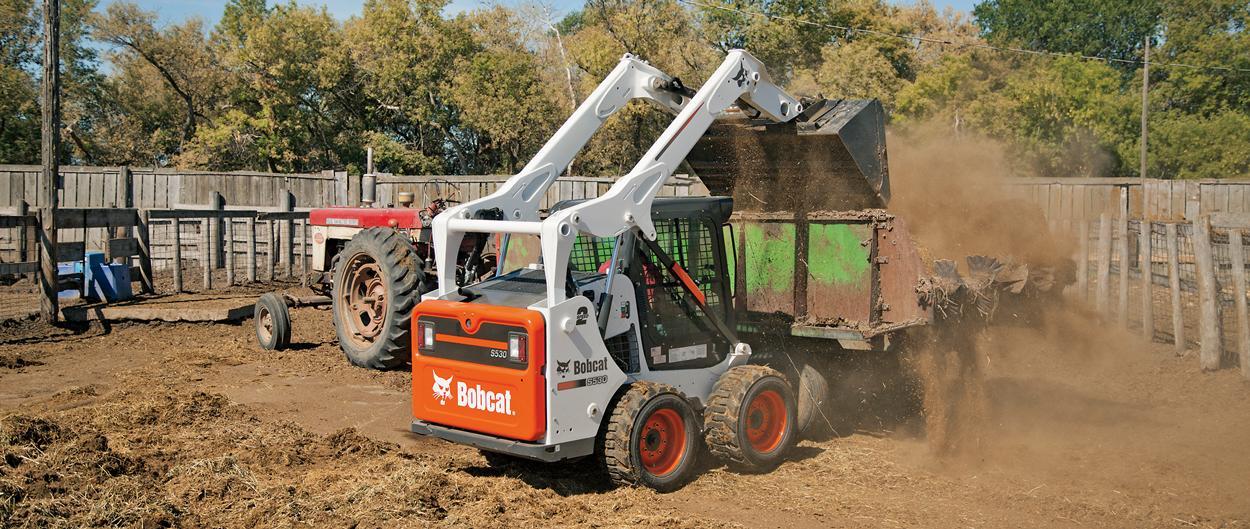 Bobcat S530 skid-steer loader with bucket loads manure.