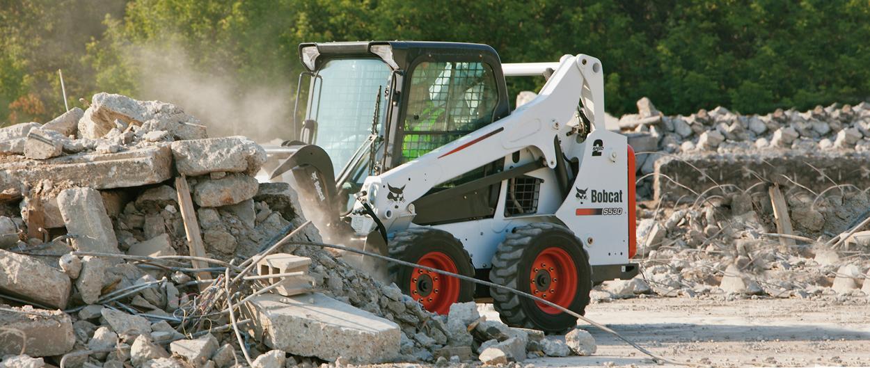 Bobcat S530 skid-steer loader with grapple attachment sorts debris.