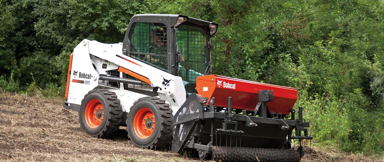 Bobcat S550 skid-steer loader with seeder attachment.