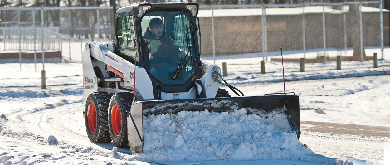 Bobcat skid-steer loader with snow pusher attachment.
