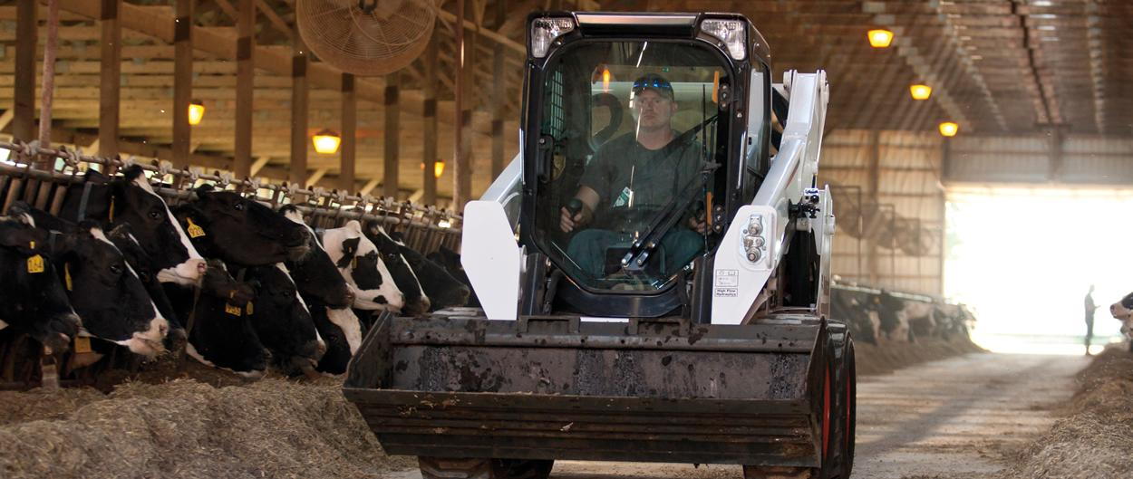 Bobcat S590 skid-steer loader works in barn.