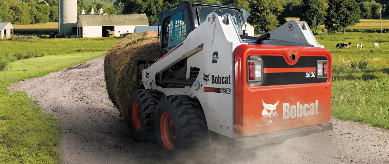Bobcat S630 skid-steer loader with a bale fork attachment carrying a bail of hay on a farm road.