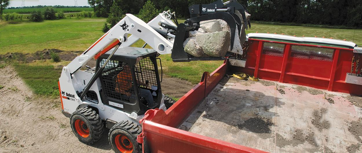Bobcat S630 skid-steer loader with grapple attachment.