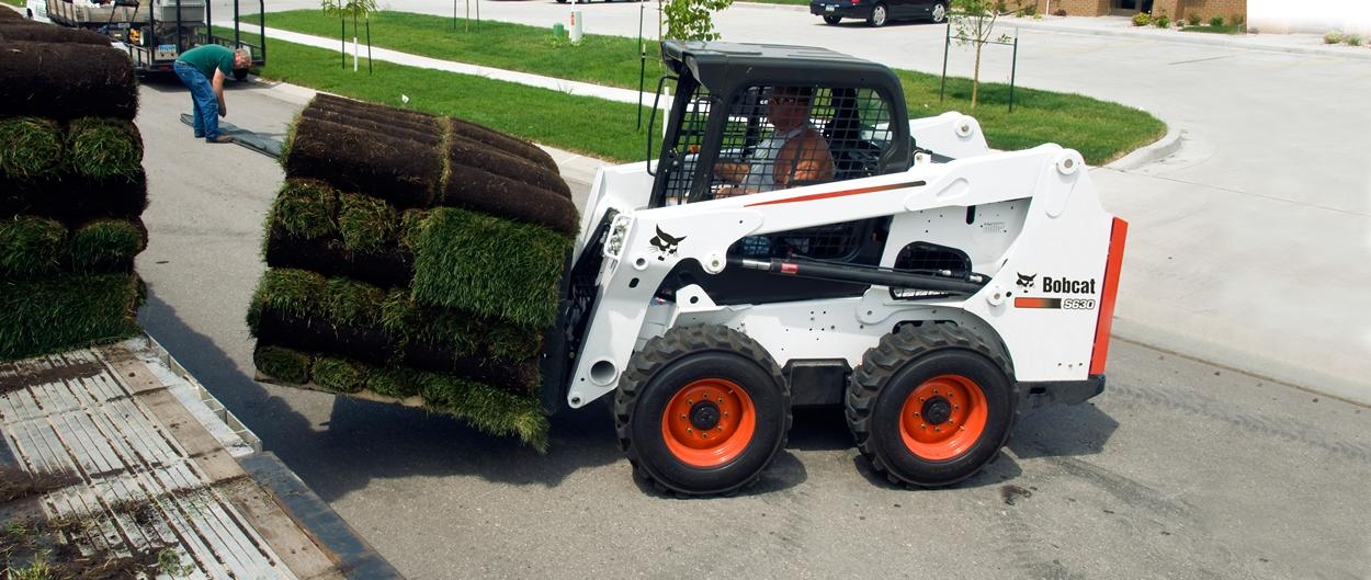 Bobcat S630 skid-steer loader with pallet fork attachment.