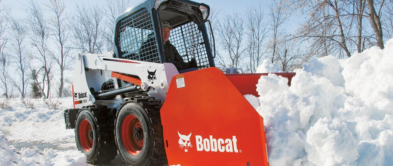 Bobcat S630 skid-steer loader with snow pusher attachment.