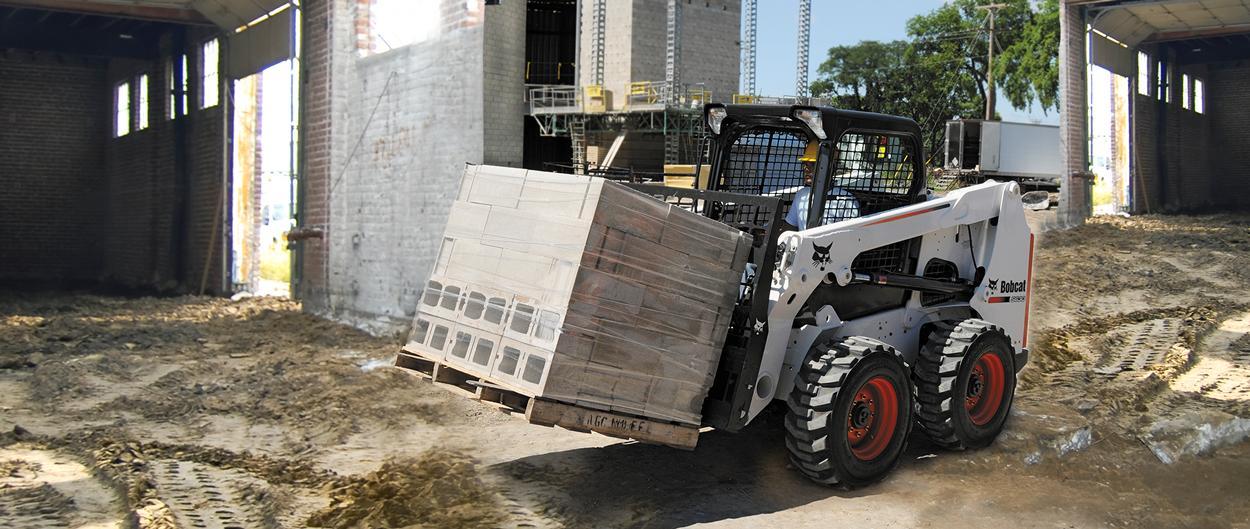 Bobcat skid-steer loader with pallet fork attachment.
