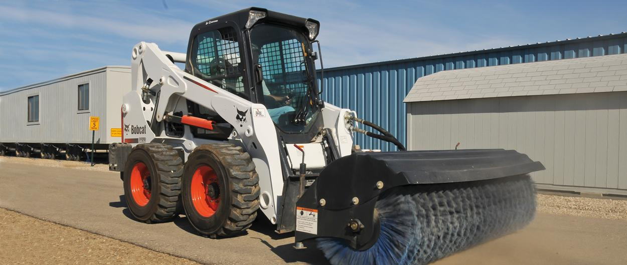 Bobcat S650 skid-steer loader with angle broom attachment.