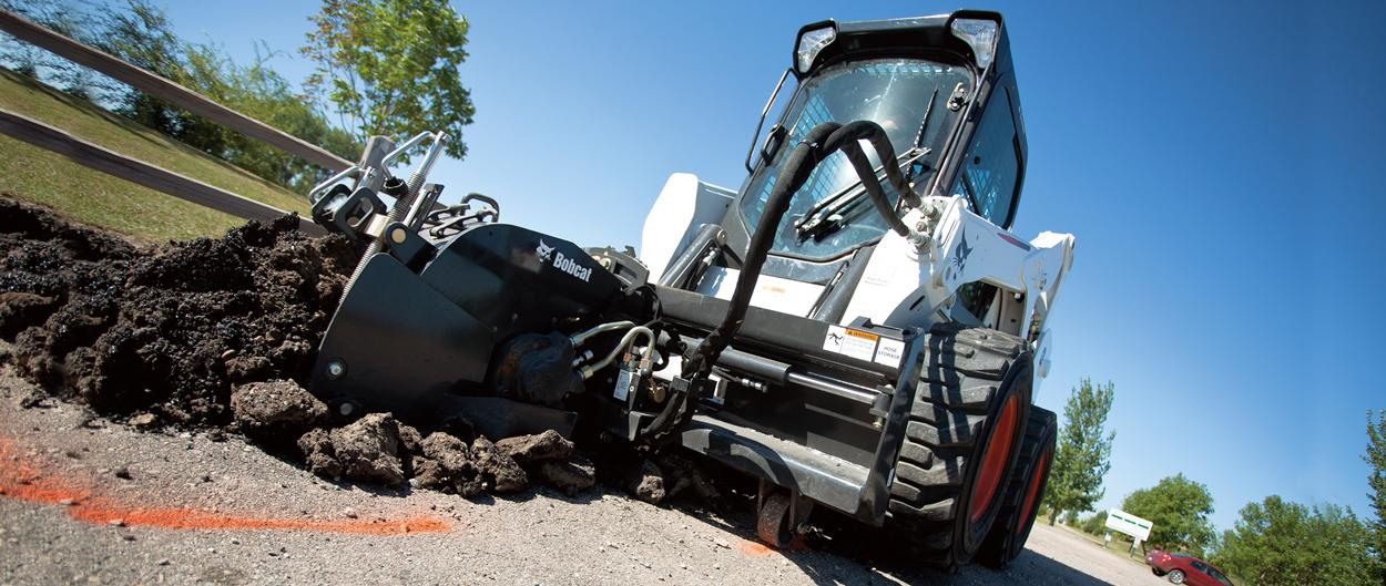 Bobcat skid-steer loader with planer attachment.