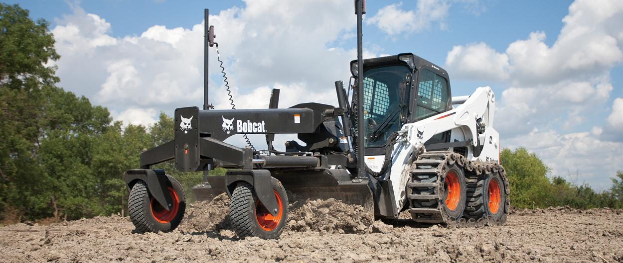 Bobcat skid-steer loader with grader attachment.
