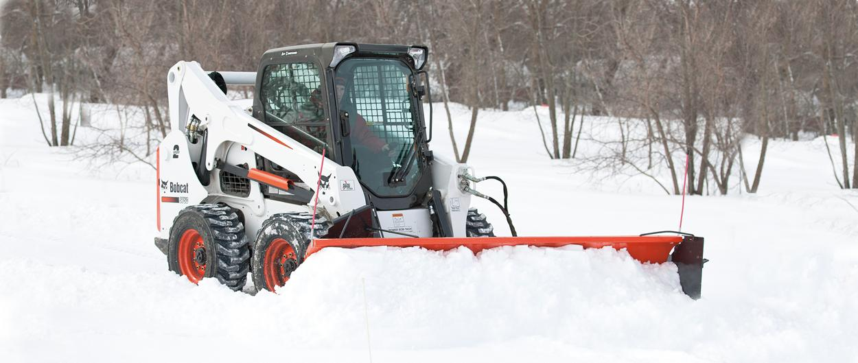 Bobcat S750 skid-steer loader with snow pusher attachment.
