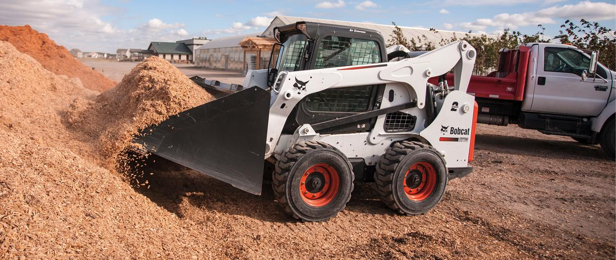 Bobcat S770 skid-steer loader loads mulch in bucket.