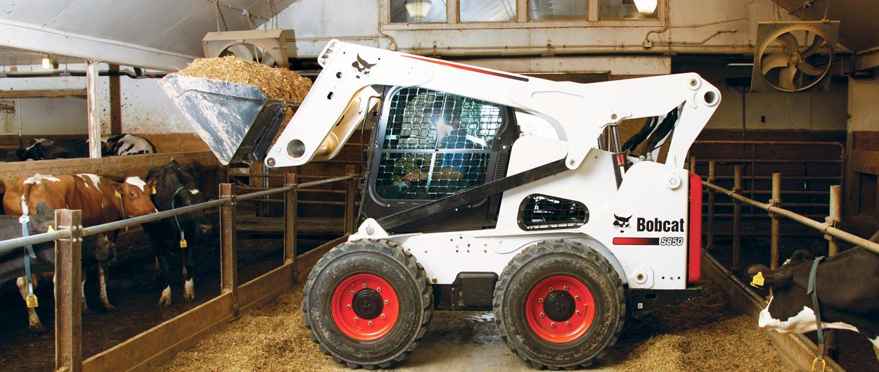Bobcat S850 skid-steer loader operates in barn.