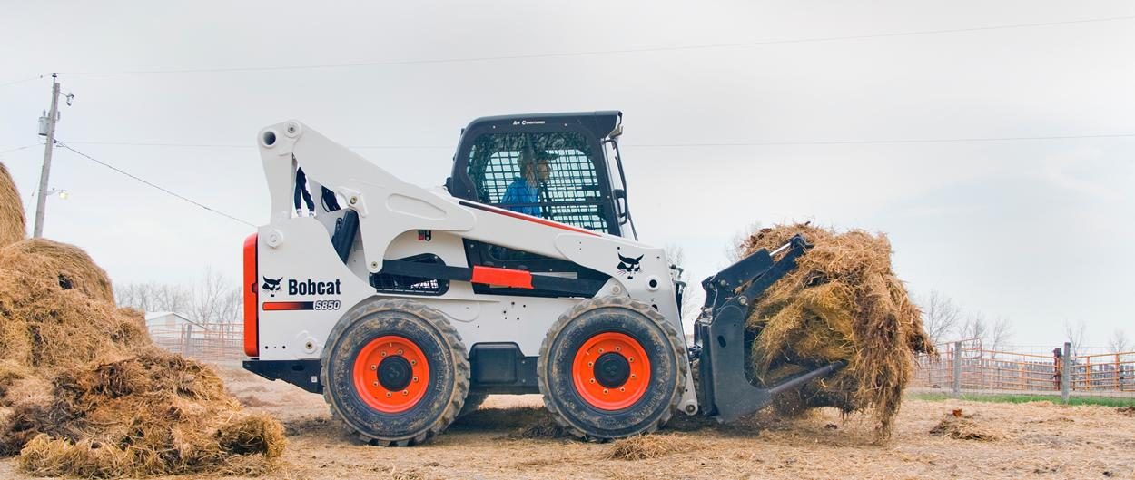 Bobcat S850 skid-steer loader hauls hay with grapple attachment.