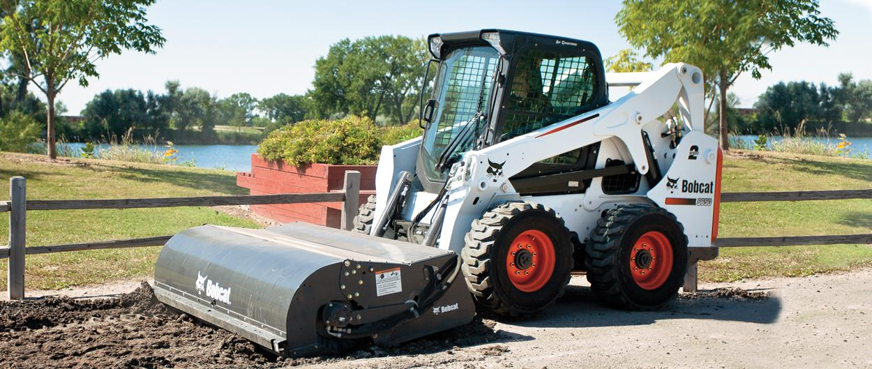 Bobcat skid-steer loader with sweeper attachment.