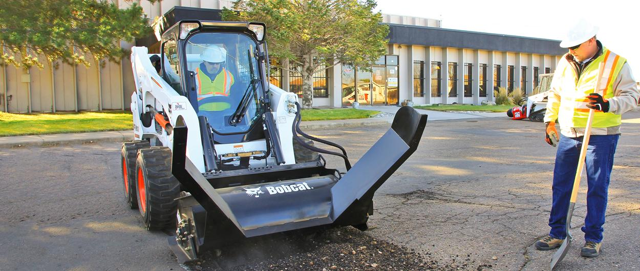 Bobcat skid-steer loader with an asphalt preservation tool attachment.