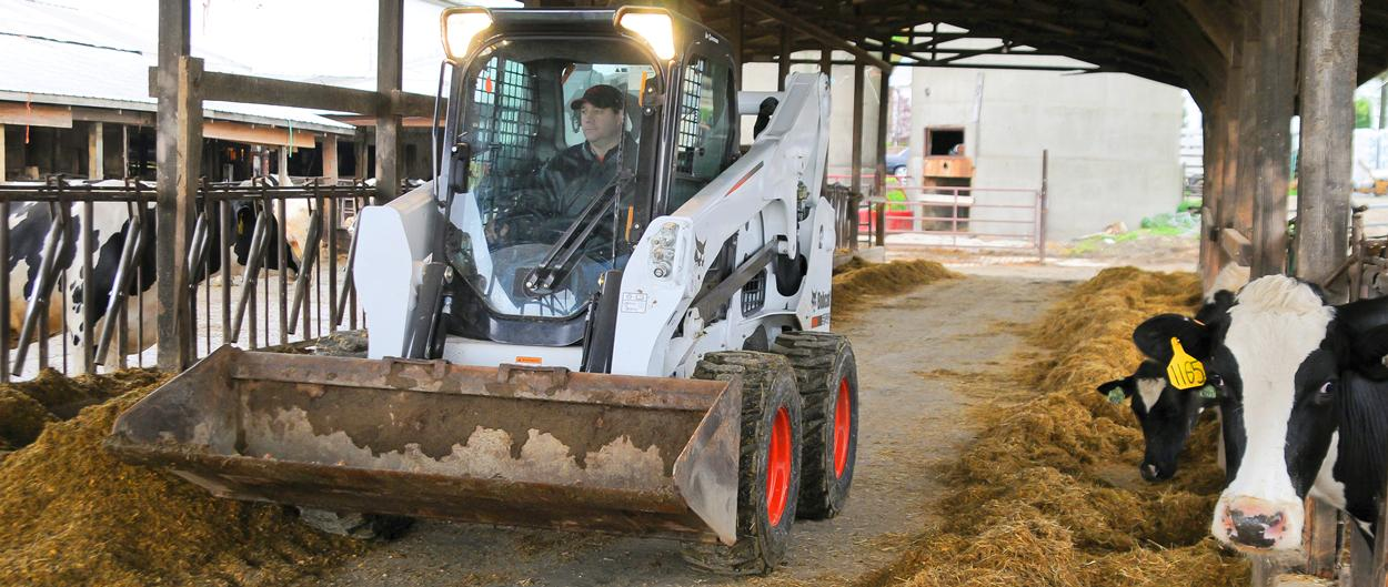 Bobcat S740 skid-steer loader navigates through barn.