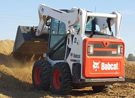 Bobcat S595 skid-steer loader dumps dirt on a construction site.