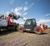 Bobcat VersaHANDLER (telehandler) telescopic tool carrier loads a log into a truck with the root grapple attachment.