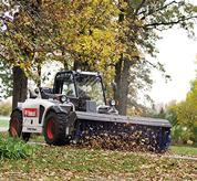 Bobcat V417 VersaHANDLER (telehandler) telescopic tool carrier sweeping leaves with angle broom.
