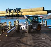 Bobcat V417 VersaHANDLER (telehandler) telescopic tool carrier carries logs with grapple attachment on a dock.