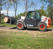 A Bobcat VersaHANDLER (telehandler) telescopic tool carrier carrying a log with root grapple attachment.