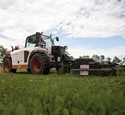 Bobcat V417 VersaHANDLER (telehandler) telescopic tool carrier with mower attachment parked on grass.