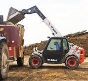 Bobcat V417 VersaHANDLER (telehandler) telescopic tool carrier loads a truck.