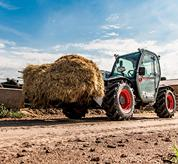 The VersaHANDLER V519 telehandler and bucket attachment working on a cattle farm.