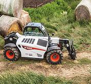 The VersaHANDLER V519 telehandler and bale fork attachment moving down a grassy path on a farm.
