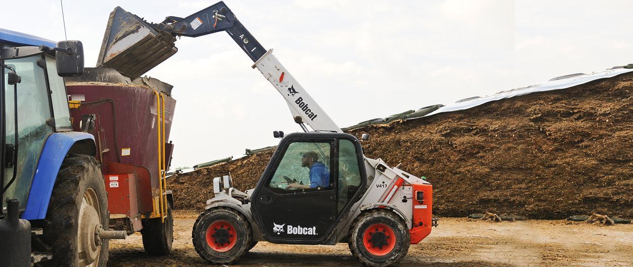 Bobcat VersaHANDLER (telehandler) telescopic tool carrier uses a bucket to lift material into a high trailer.