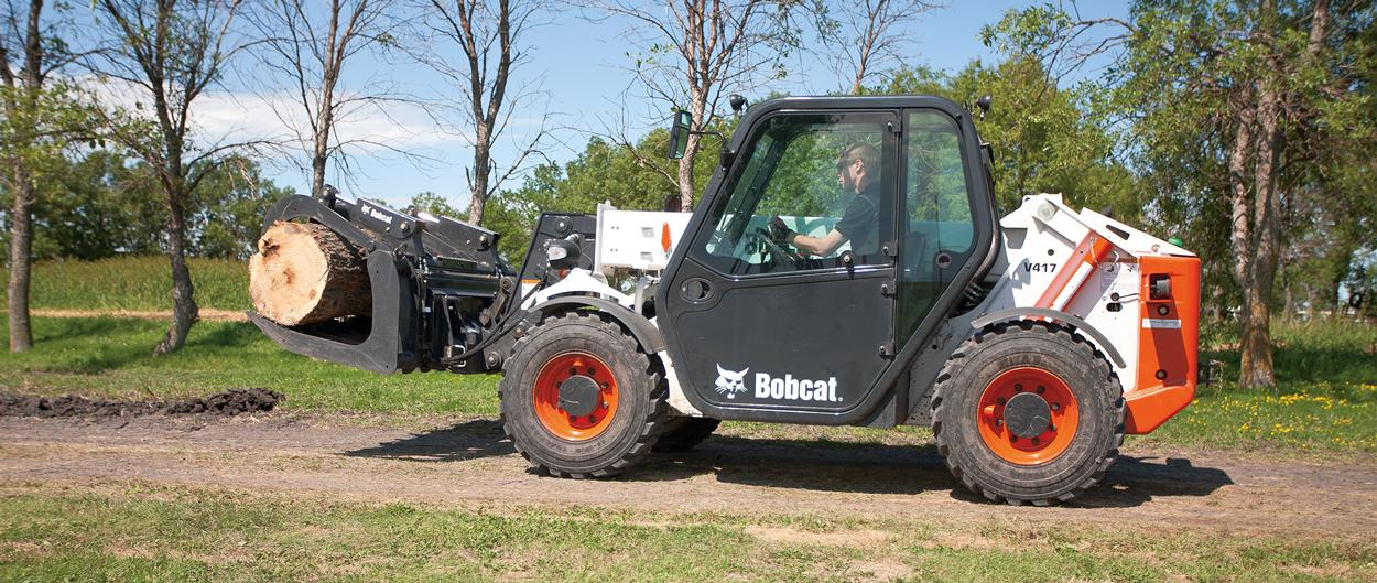 A root grapple attachment on the Bobcat V417 VersaHANDLER (telehandler) telescopic tool carrier is used to carry a log.