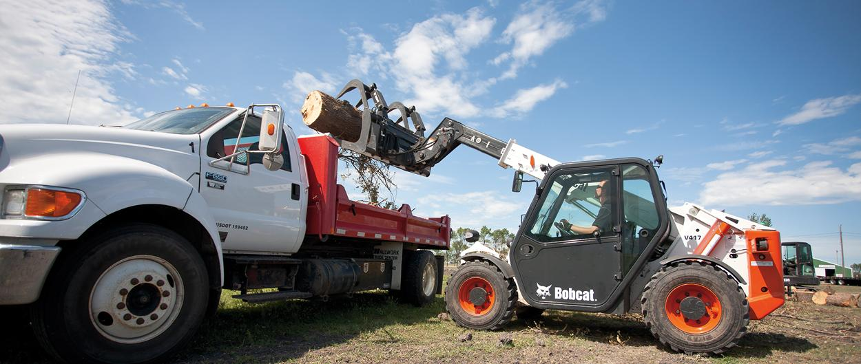 V417 VersaHANDLER telehandler with bucket attachment lifts a large log into a high-sided truck with a grapple attachment.