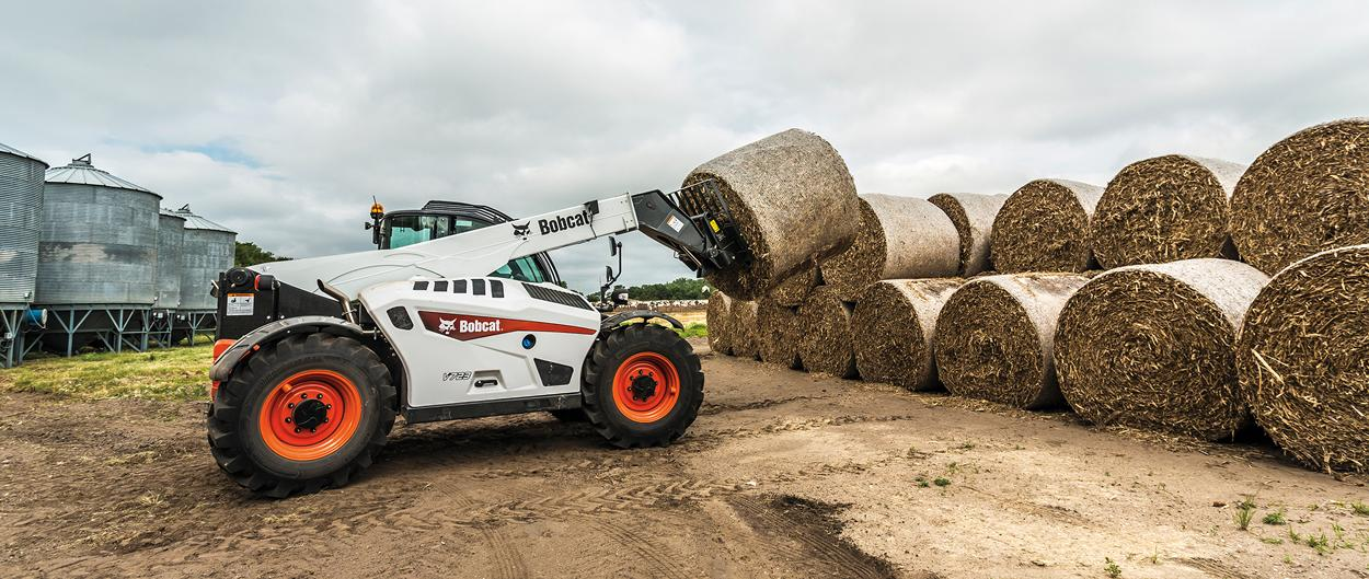 Bobcat V723 VersaHANDLER telescopic tool carrier (telehandler) lifts hay bales on a stack with a bale fork.