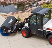 Toolcat 5600 with angle broom maneuvers around a tight sidewalk space on a college campus.